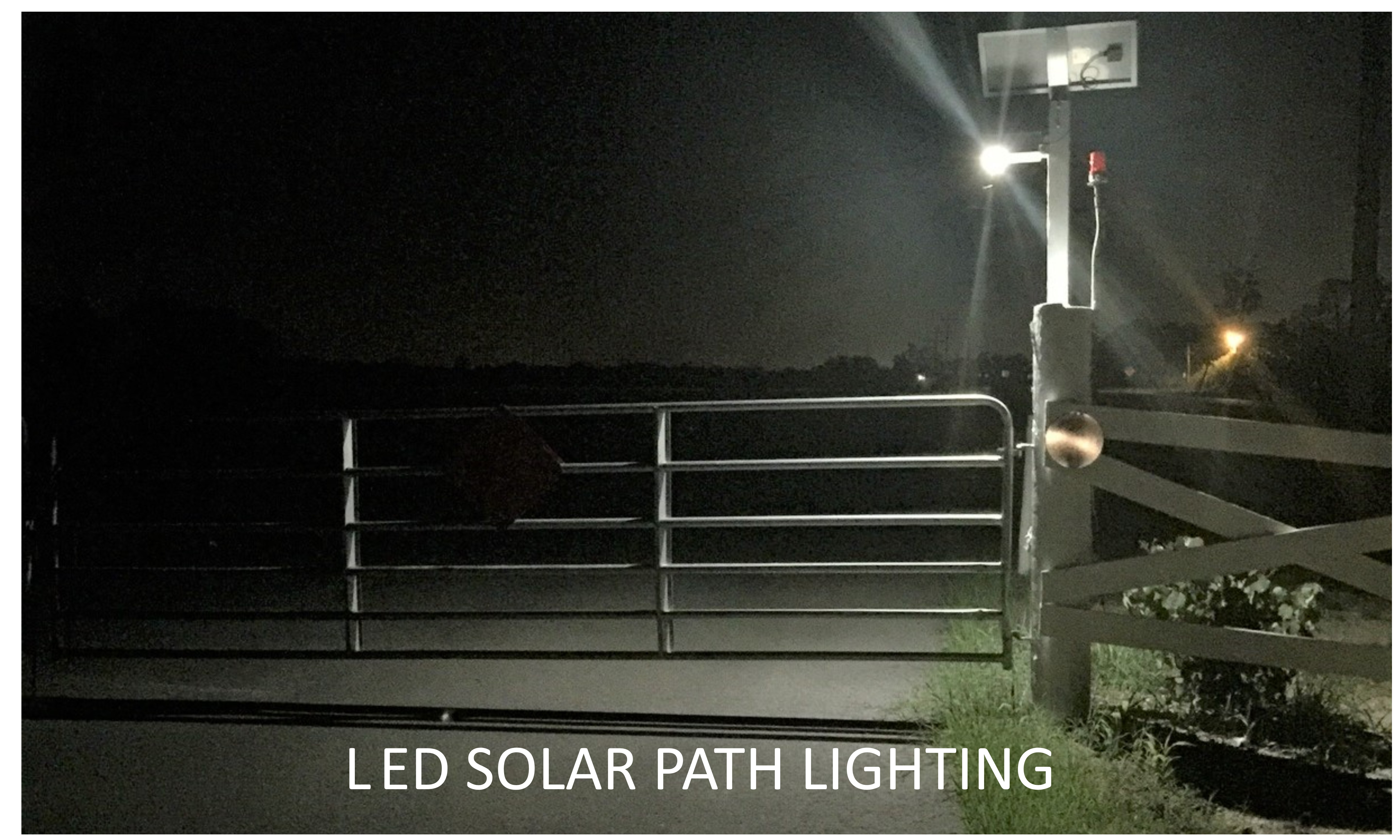 This is a photo of a gated entrance that is lighted by a solar path light.
